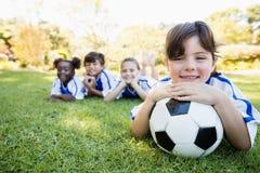 Fermez-vous vers le haut de la vue de la fille se trouvant sur le plancher avec son équipe de football Photo libre de droits