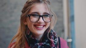 Fermez-vous vers le haut de la vue de la jeune fille magnifique dans un équipement occasionnel regardant vers l'appareil-photo et clips vidéos