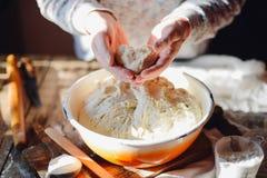 Fermez-vous vers le haut de la vue de la pâte de malaxage de boulanger Pain fait maison Mains pré Photo stock