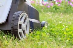 Fermez-vous vers le haut de la vue de la tondeuse à gazon sur l'herbe verte dans le jardin Images stock