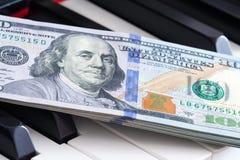 Fermez-vous vers le haut de la vue des des billets de banque cent dollars sur des clés de piano Image stock