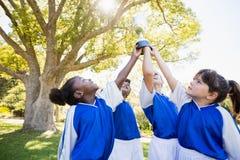 fermez-vous vers le haut de la vue des bras d'équipe de football d'enfants dans le ciel avec la tasse Images libres de droits