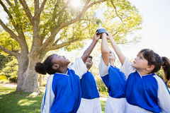 fermez-vous vers le haut de la vue des bras d'équipe de football d'enfants dans le ciel avec la tasse Photo stock