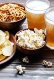 Fermez-vous vers le haut de la vue des casse-croûte et de la bière des plats pendant la partie Photo libre de droits