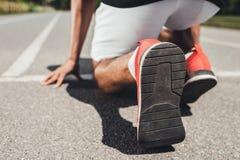fermez-vous vers le haut de la vue des chaussures de course du sprinter masculin en position de départ images stock