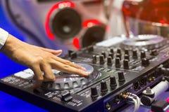 Fermez-vous vers le haut de la vue des contrôles de main du ` s du DJ sur la plate-forme la nuit PS du DJ Image stock