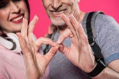 Fermez-vous vers le haut de la vue des couples de sourire montrant le signe correct ensemble Photographie stock