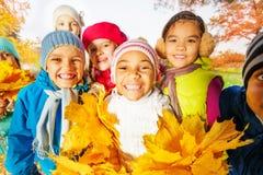 Fermez-vous vers le haut de la vue des enfants mignons heureux avec le groupe de feuilles Images stock