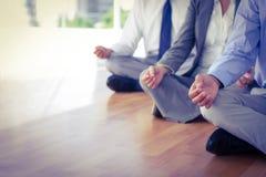 Fermez-vous vers le haut de la vue des gens d'affaires faisant le yoga Photographie stock libre de droits
