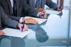 Fermez-vous vers le haut de la vue des mains d'homme d'affaires écrivant sur le papier Images libres de droits