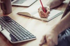 Fermez-vous vers le haut de la vue des mains d'indépendant écrivant avec le crayon dans le noteboo Images stock
