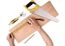 Fermez-vous vers le haut de la vue des mains d'un homme mesurant la planche en bois avec la ligne de bande, sur le fond blanc Photos libres de droits