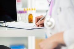 Fermez-vous vers le haut de la vue des mains femelles de médecins de médecine remplissant patient m image libre de droits