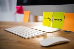 fermez-vous vers le haut de la vue des notes collantes colorées avec le lettrage de vente et de stratégie sur l'écran d'ordinateu Images stock
