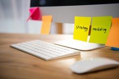 fermez-vous vers le haut de la vue des notes collantes colorées avec le lettrage de vente et de stratégie sur l'écran d'ordinateu Photographie stock
