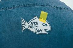 fermez-vous vers le haut de la vue des poissons faits par papier avec la bande collante sur des jeans chemise, imbéciles d'avril photos libres de droits