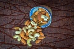 Fermez-vous vers le haut de la vue des raisins secs nuts d'amandes d'anarcadier dans une cuvette sur la table en bois photographie stock libre de droits