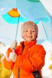 Fermez-vous vers le haut de la vue du garçon de sourire avec le parapluie Image libre de droits