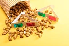 Fermez-vous vers le haut de la vue du maïs éclaté et des verres 3D sur le jaune Photographie stock libre de droits