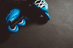 Fermez-vous vers le haut de la vue du patin ou du roller intégré bleu de patins de rouleau sur le backgroung grunge teinté par ob Image stock