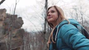 Fermez-vous vers le haut de la vue du randonneur blond attirant marchant dans la forêt d'automne, en observant le paysage Belles  clips vidéos