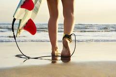 Fermez-vous vers le haut de la vue du surfer marchant le long de la plage vers le ressac Photo stock