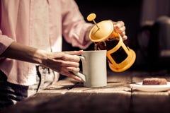 Fermez-vous vers le haut de la vue du thé se renversant de femme dans la tasse blanche Photos libres de droits