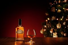 Fermez-vous vers le haut de la vue du verre avec le whiskey sur le dos de couleur label fait par individu Images libres de droits