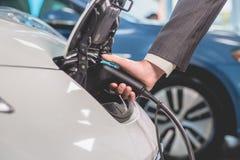 Fermez-vous vers le haut de la vue de l'homme rechargeant la voiture électrique Images libres de droits