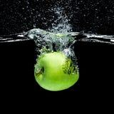 fermez-vous vers le haut de la vue de la pomme verte tombant dans l'eau photo libre de droits