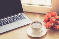 Fermez-vous vers le haut de la vue sur l'intérieur de bureau de travail avec une tasse d'ordinateur portable et de café de matin  Photos stock