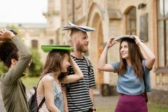 Fermez-vous vers le haut de la vue sur les étudiants multi-ethniques tenant des livres sur leurs têtes Photographie stock libre de droits