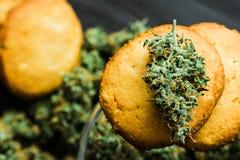 Fermez-vous vers le haut de macro biscuits avec des cannabis et de bourgeons de marijuana sur la table employez CBD photo stock