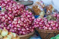 Fermez-vous vers le haut de petits oignons blancs rouges frais au marché, faisant cuire la matière Image libre de droits