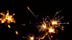 Fermez-vous vers le haut de plusieurs cierges magiques de feu d'artifice au-dessus de noir Images libres de droits