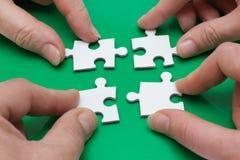 Quatre personnes avec le puzzle Photo libre de droits
