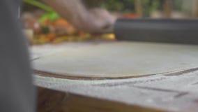 Fermez-vous vers le haut de rouler la pâte mince pour les pâtes fraîches à la table en bois Pâte de roulement de cuisinier de che clips vidéos