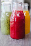Fermez-vous vers le haut de trois bouteilles de smoothies de fruit Photographie stock