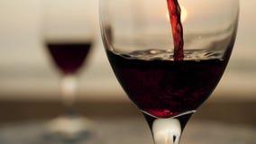 Fermez-vous vers le haut de verser le verre de vin rouge au coucher du soleil sur le paysage de plate-forme de vue de bord de la  banque de vidéos