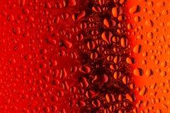 Fermez-vous vers le haut des baisses de l'eau sur la surface en verre rouge Image stock