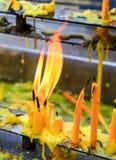 Fermez-vous vers le haut des bougies jaunes avec la flamme dans le temple Photos stock
