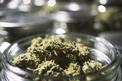 Fermez-vous vers le haut des bourgeons de marijuana dans le pot en verre avec le fond trouble Photos libres de droits