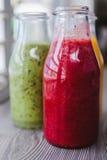 Fermez-vous vers le haut des bouteilles de smoothies de fruit Kiwi Fraise Photo libre de droits