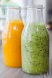 Fermez-vous vers le haut des bouteilles de smoothies de fruit Kiwi Orange Image libre de droits