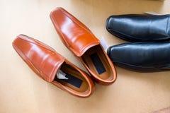 Fermez-vous vers le haut des chaussures en cuir brunes avec les chaussures noires Images stock