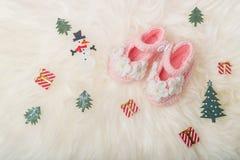Fermez-vous vers le haut des chaussures tricotées par bébé sur le fond couvrant blanc Carte de voeux de Joyeux Noël et de bonne a Image stock