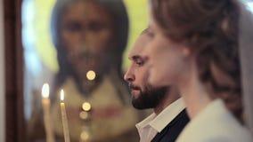 Fermez-vous vers le haut des couples de mariage dans une église avec des bougies au fond d'icône de Jesus Christ banque de vidéos