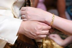 Fermez-vous vers le haut des couples mettant la chaîne d'or pour l'engagement Photographie stock libre de droits