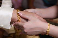 Fermez-vous vers le haut des couples mettant la chaîne d'or pour l'engagement Photographie stock