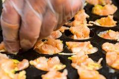 Fermez-vous vers le haut des crevettes roses de cuisson dans la moule avec des trous photos stock